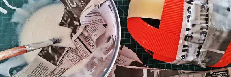 A papier mache mask being made with glue and newspaper.