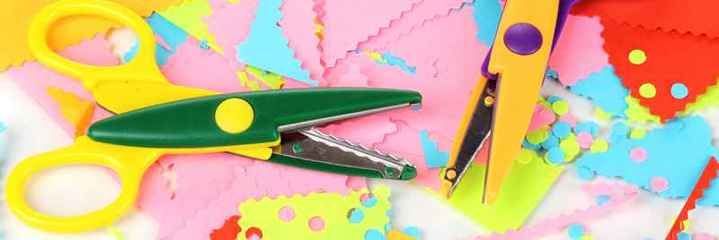 Colourful crafting scissors sitting on bright paper.