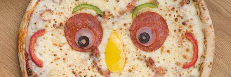 A pizza with toppings arranged in the shape of a face.