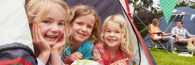 Three girls sitting in a tent camping while their parents sit nearby.