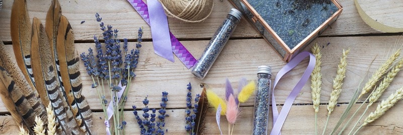Colourful feathers, lavender, and glitter laid out on a wooden table.