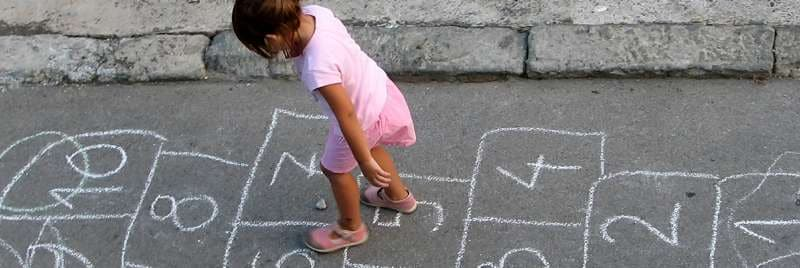 A girl playing hopscotch in the street.