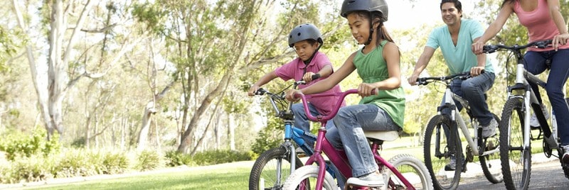 Happy family riding bikes in a park.