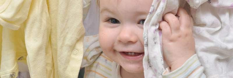 A happy baby surrounded by clean baby clothes.