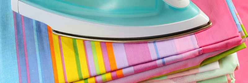 An iron placed on top of colourful stacked sheets.