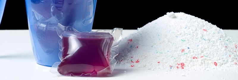 Close up of spilled washing powder, washing capsules, and a scoop.