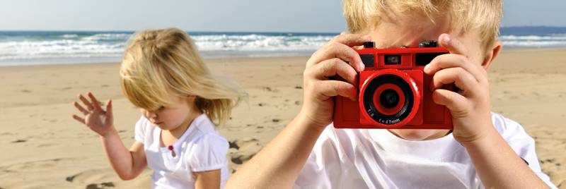 A boy holds up a camera while his sister plays on a beach.
