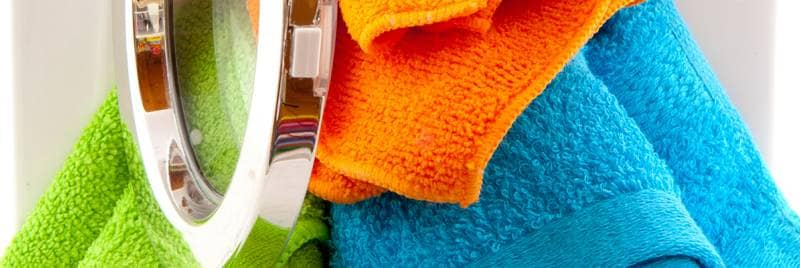 Colourful towels spilling out of a washing machine.