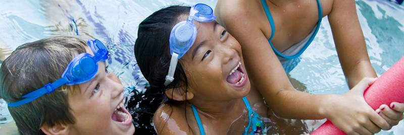 Children happily playing in a swimming pool while wearing goggles.
