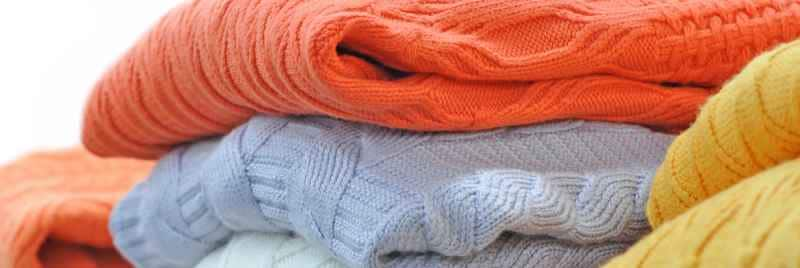 A pile of colourful jumpers stacked up.