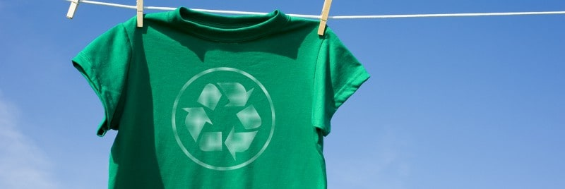 A green t-shirt with a recycling symbol on it, hanging on out to dry.