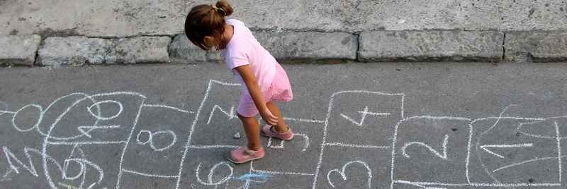 Little girl playing hopscotch in the street.