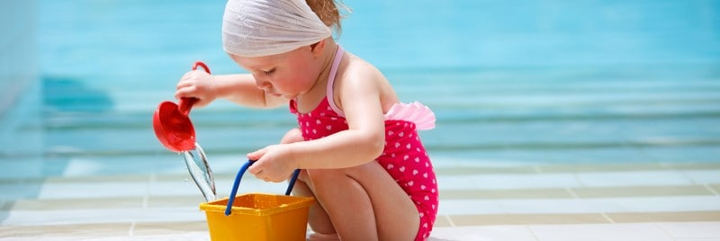 A girl playing with water near a swimming pool using a bucket and ladle.