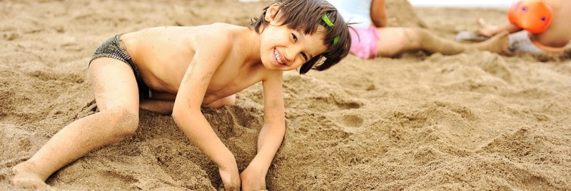 Happy boy digs a hole in the sand on a beach while other children play nearby.