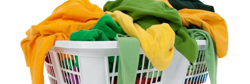 An image of yellow and green clothes in a laundry basket.