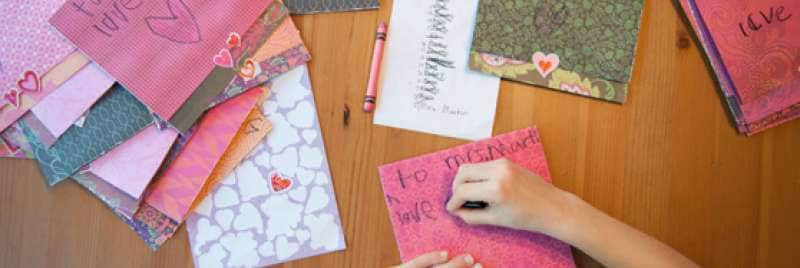 A girl creating homemade cards and letters.