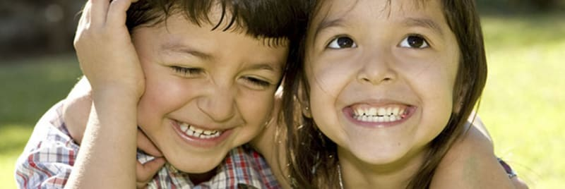 Two children smiling outside together.
