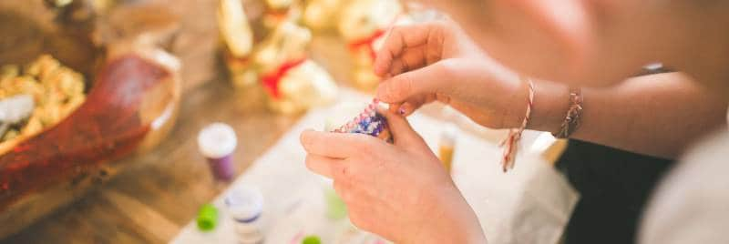 Child decorating an egg with glue, beads and glitter.