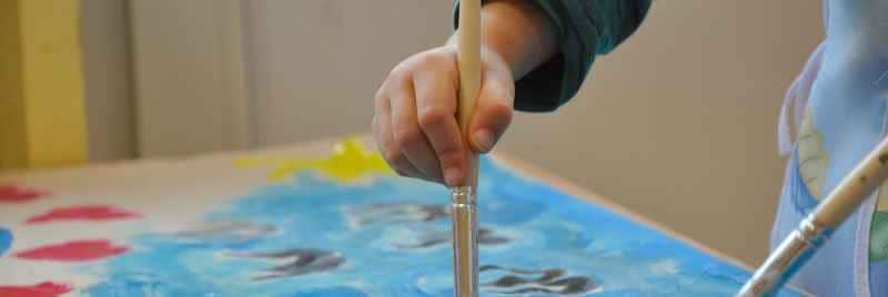 A child painting a picture using acrylic paint.