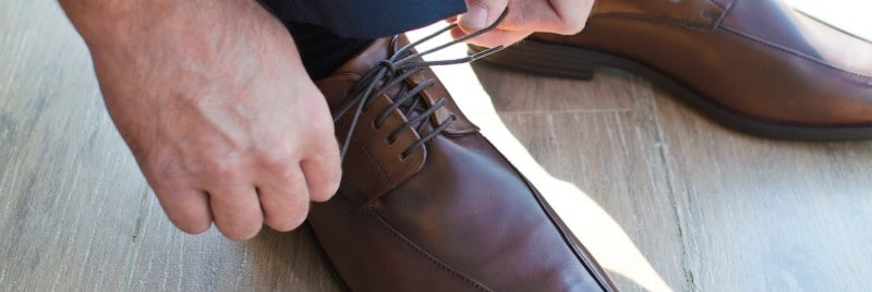 A man tying the shoelaces of his brown polished shoes.