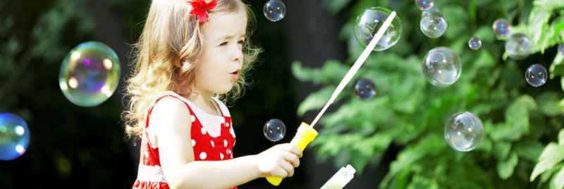 Young girl in a red and white spotted dress playing with a bubble wand in the garden.