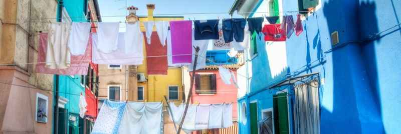 Washing lines hanging between houses on a colourful street.