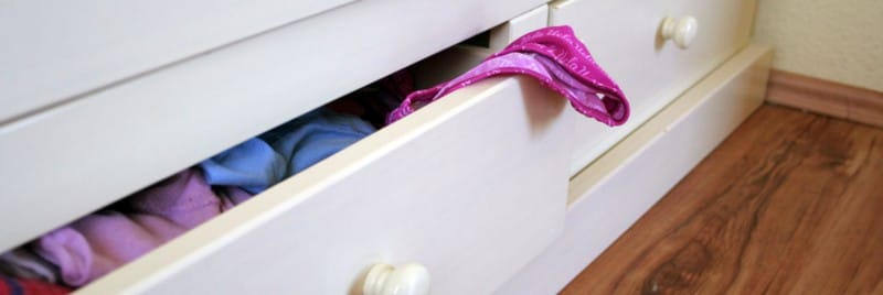 A pink piece of clothing protruding from an open drawer.
