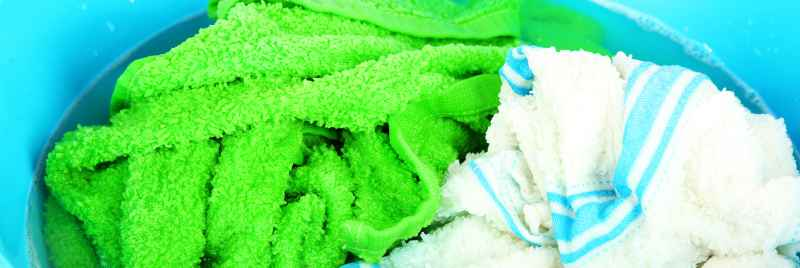 Towels soaking in a blue bowl with water and detergent.