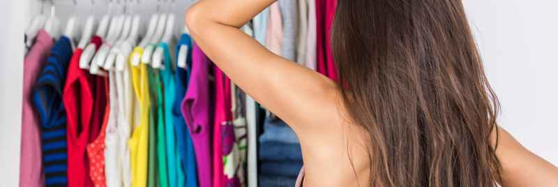 A woman standing in front of her open wardrobe, contemplating what to wear.