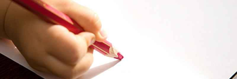 Child's hand holding a red-coloured pencil over a sheet of white paper.