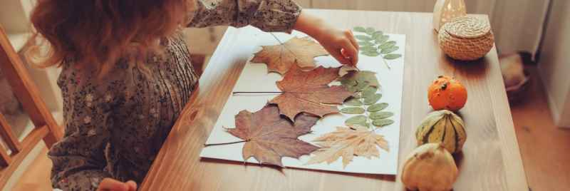 A girl arranging dried leaves on a sheet of white paper.