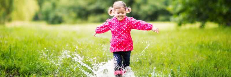 A girl happily walking through puddles in a field.