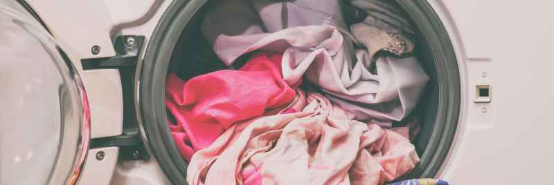 A general image of a washing machine filled with pink clothes.