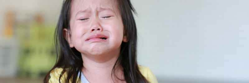A young girl in a yellow top crying.