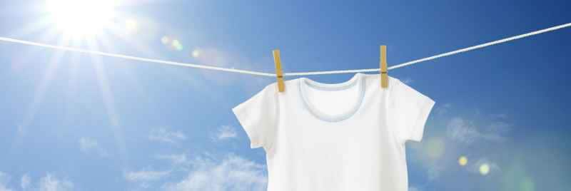 A white t-shirt pegged to a washing line drying in the sun.
