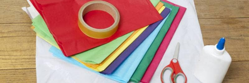 General image of many pieces of  paper in different color places on table with scissors and tape.