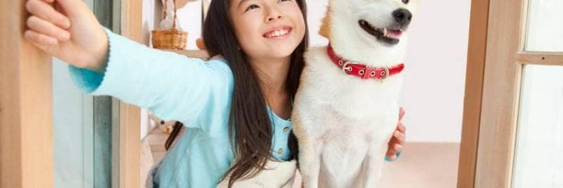 A girl and her dog stand by open window looking outside of room.