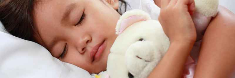 General image of a innocent girl sleeping with tightly holding teddy bear on bed.
