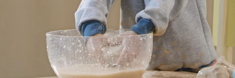 The image shows a kid playing pottery in the big bowl.