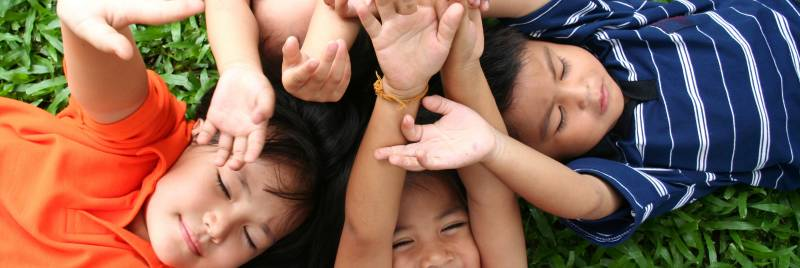 Children lying on grass raising their hands to the sky.
