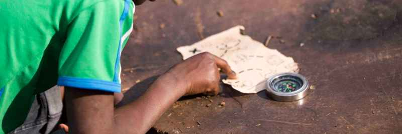 A child using a map and compass to find treasure.