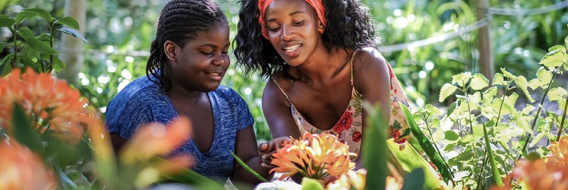 A mother and daughter staring at a flower.