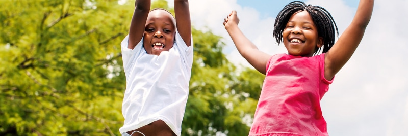 Two kids are jumping high and smiling.