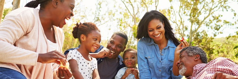 A family sitting outside smiling.