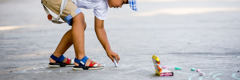 A child drawing on the street floor.