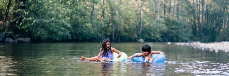 A girl and boy floating down a river on rubber rings.